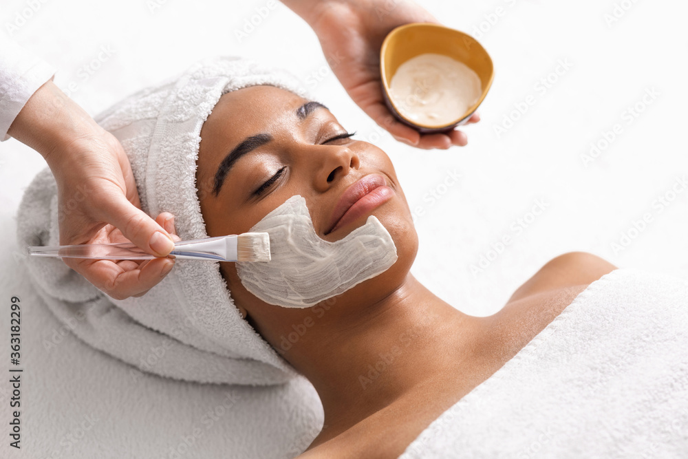 Fototapeta Top view of beauty therapist applying face mask