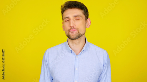 Fotomural Handsome bearded man flirts licking lips with teeth on yellow background with copy space