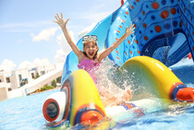 Little Girl On Slide At Water Park. Summer Vacation