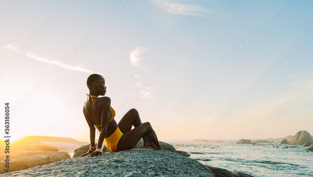 Fototapeta African woman relaxing on a rock at the beach