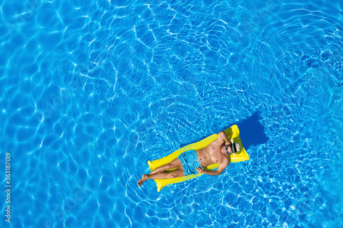 Fototapeta Young man with inflatable mattress in swimming pool, top view. Space for text obraz