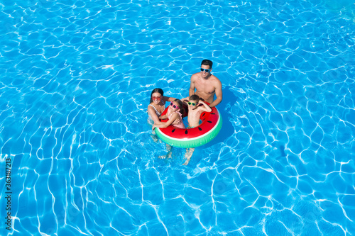 Fototapeta Happy family with inflatable ring in swimming pool. Summer vacation obraz