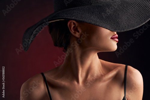 Fototapety, obrazy: profile portrait of a beautiful tanned girl with professional makeup, red lips on a burgundy background in a black dress with straps, a black hat that covers half of her face