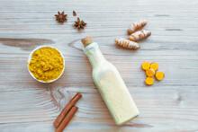 Goldene Milch Mit Kurkuma In Einer Glasflasche, Zimtrinde, Sternanis Und Einem Schüssel Mit Pulver Auf Einem Holz Hintergrund. Draufsicht, Aryuveda, Indien, Zutaten.