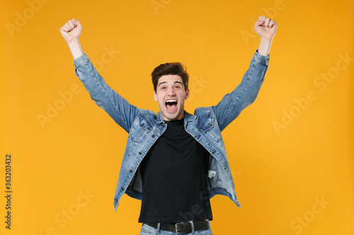 Valokuvatapetti Screaming young man guy in casual denim jacket posing isolated on yellow background studio portrait