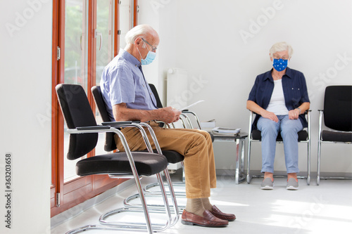 Senior woman and man sitting with face masks in a bright waiting room of  a hosp Fototapeta