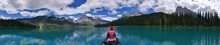 Rear View Of Woman In Boat On Lake Against Mountains And Sky