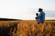 farmer and his son walking fields of wheat