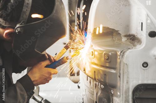 Photo Worker in mask welds car in auto service of bodywork.