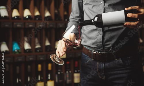 Fototapeta Close up shot of sommelier pouring red wine from bottle in glass on underground cellar background obraz