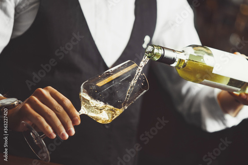 Fototapeta Close up photo, sommelier pouring white wine into wineglasses. obraz