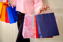 Midsection Of Woman Holding Shopping Bags While Standing Against Wall