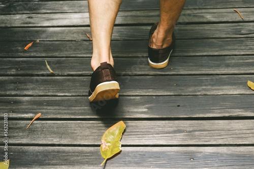 Fotografia Low Section Of Man Walking On Boardwalk