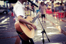 Midsection Of Man Playing Guitar While Singing On Street