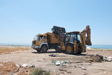 Tractor And A Big Range Truck  Collecting Waste In The Beach