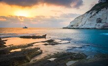 Beautiful Sunset With White Cliffs Of Rosh HaNikra Grottoes, On The Border Between Israel And Lebanon, On The Coast Of The Mediterranean Sea, With Israeli Navy Border Patrol Boat; Western Galillee