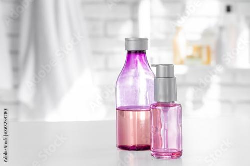 Fototapeta Cosmetic bottles against white bathroom wall background obraz