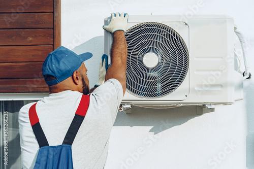 Fototapeta Repairman in uniform installing the outside unit of air conditioner obraz