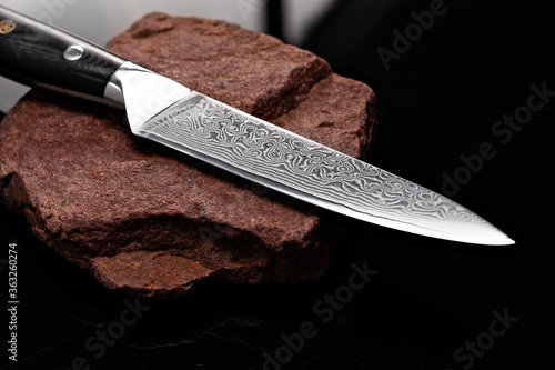 Fotografering A large kitchen knife with a black handle on a dark background