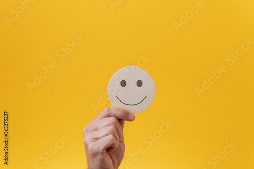 Fototapeta Male hand showing a wooden cut circle with smiling face on it obraz