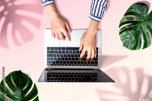 Fototapeta Person using a laptop computer with tropical leaves from above obraz