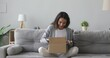 Happy young woman customer sit on sofa open parcel carton box satisfied with online shop order delivery at home, smiling girl consumer unpack package receive good purchase by postal shipping concept