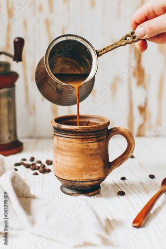 Fototapeta Coffee with milk is poured into a mug obraz