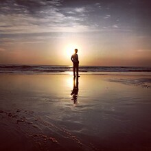 Silhouette Teenage Boy Standing At Beach Against Sky During Sunset