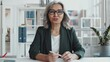 Beautiful senior businesswoman in formalwear and glasses sitting at desk in the office, looking at camera and having discussion while video calling during workd