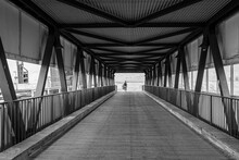 Rear View Of Woman Walking In Covered Bridge