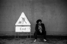 Bearded Man Sitting By Sign Against Wall
