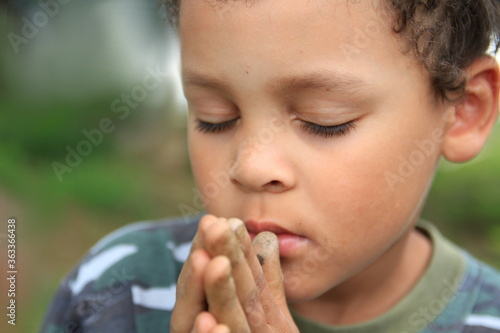 Leinwand Poster boy praying to God with hands together and closed eyes stock photo