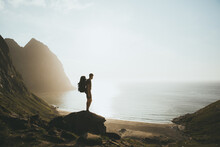 High Angle View Of Man Standing On Rock Against Sea