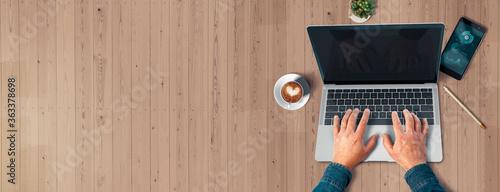 Escritorio madera. Manos sobre un laptop. Realizando tele trabajo Fotobehang