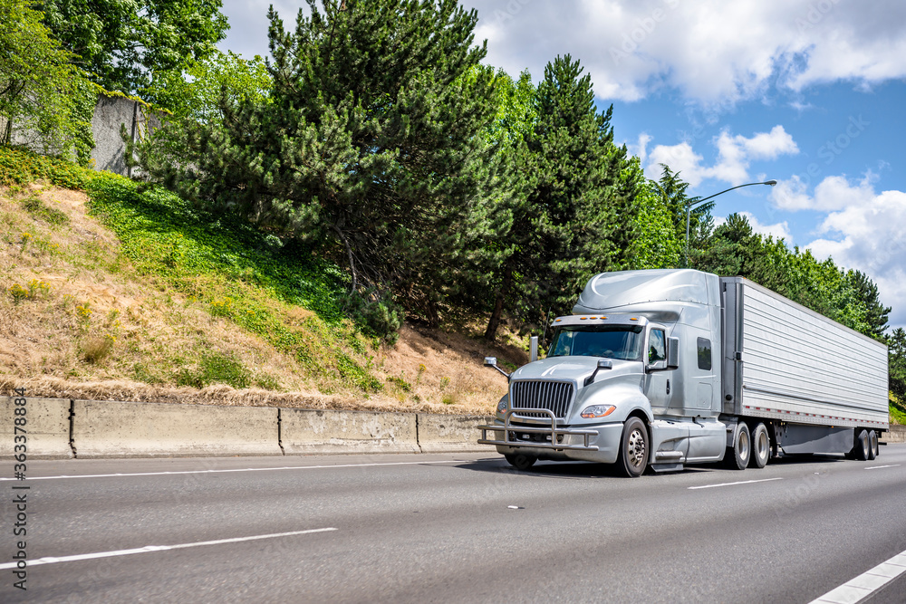 Fototapeta Gray big rig semi truck with grille guard transporting commercial cargo in refrigerator semi trailer driving on the wide highway road to point of delivery