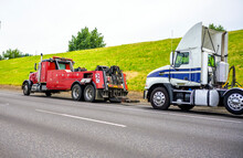 Red Big Rig Semi Towing Truck Prepare To Tow Broken White Big Rig Semi Tractor Standing Out Of Service On The Road Side