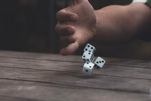 Man Rolling Dice On Wooden Table
