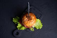 Fresh Lettuce Leaves On  Sides, Black Background, Top View Big Burger With  Fork Inside,