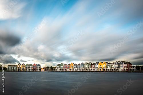 Fototapeta View Of Buildings By Lake Against Cloudy Sky