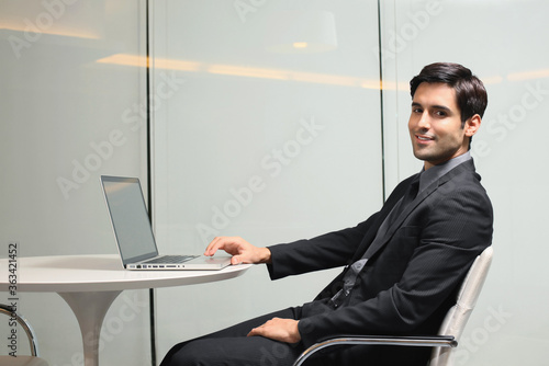 Businessman using laptop and smiling Wallpaper Mural