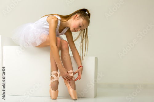 Fototapeta Girl ballerina puts on pointe shoes. The concept of dancing.