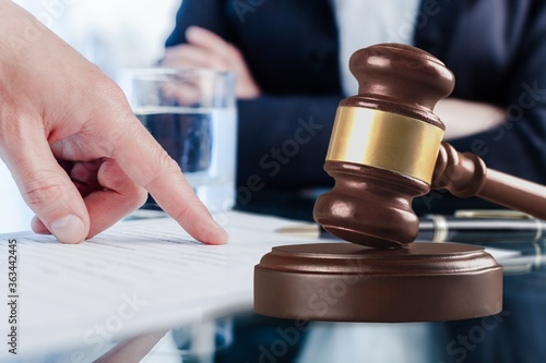 Fototapeta Male hand pointing a place to sign a paper and wooden gavel obraz