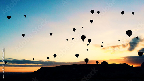 Fotografiet Low Angle View Of Silhouette Hot Air Balloons Against Sky During Sunset
