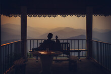 Rear View Of Silhouette Man Sitting In Balcony During Sunset