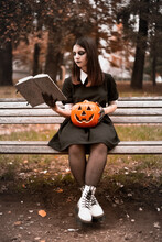 Young Woman In Halloween Costume Reading Book While Sitting On Park Bench