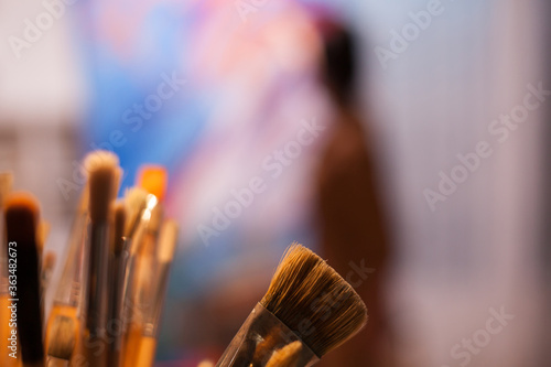 Fotografía Close up of paint brushes and artist in the background