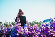 Woman Standing By Purple Flowering Plants Against Sky