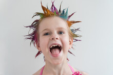 The Child Looks Directly Into The Camera With Large Eyes. A Girl With Multicolored Hair In An Evening Dress. Party, Holiday, Or Birthday. Humor.