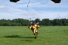 Skydiving. A Skydiver Is Landing On The Field.