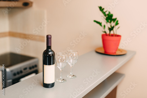 A bottle of wine and two empty glasses on the bar in the kitchen.